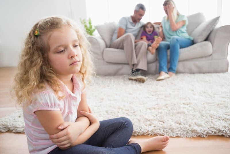 Συνεδρίαση κοριτσιών στο πάτωμα ενώ γονείς που απολαμβάνουν με τον αδελφό στοκ εικόνες