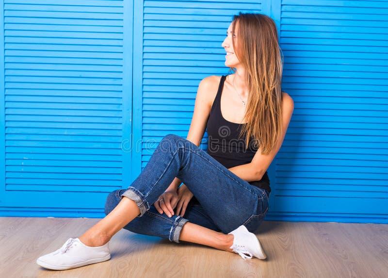 Συνεδρίαση κοριτσιών Hipster στο πάτωμα στο μπλε κλίμα στοκ εικόνα με δικαίωμα ελεύθερης χρήσης