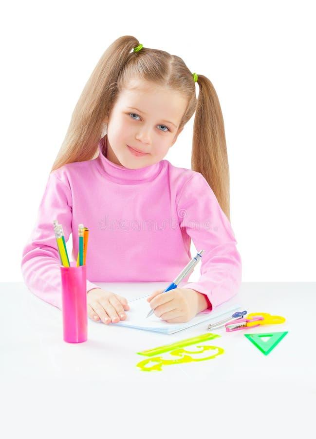 Συνεδρίαση κοριτσιών Litli στον πίνακα και γράψιμο με το isola μανδρών ballpoint στοκ φωτογραφία με δικαίωμα ελεύθερης χρήσης
