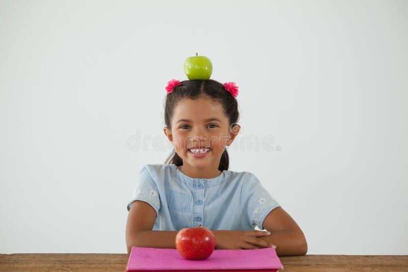 Συνεδρίαση μαθητριών με το πράσινο μήλο στο κεφάλι της στο άσπρο κλίμα στοκ εικόνες