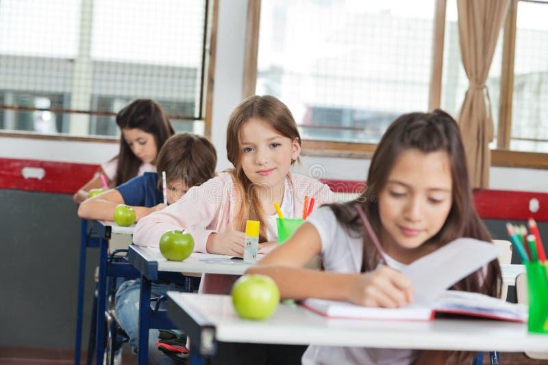 Συνεδρίαση μαθητριών στο γραφείο με τους συμμαθητές στο Α στοκ φωτογραφία με δικαίωμα ελεύθερης χρήσης