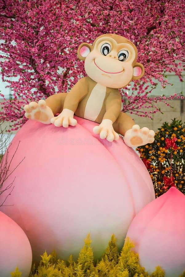Συνεδρίαση μασκότ πιθήκων στο ροδάκινο - κινεζική νέα διακόσμηση έτους στοκ φωτογραφίες