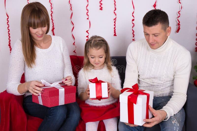 Συνεδρίαση μητέρων, πατέρων και κορών στον καναπέ και το christma ανοίγματος στοκ εικόνα με δικαίωμα ελεύθερης χρήσης