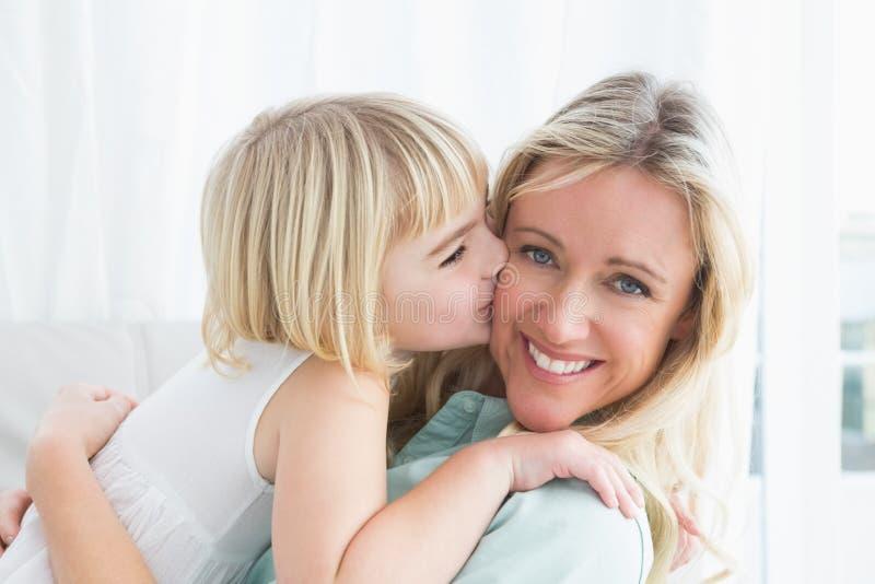 Συνεδρίαση μητέρων στον καναπέ με την κόρη της που φιλά το μάγουλό της στοκ εικόνα
