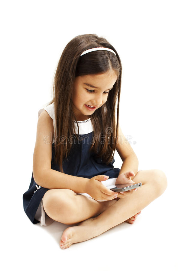 Συνεδρίαση μικρών κοριτσιών και παιχνίδι με το smartphone στοκ εικόνα