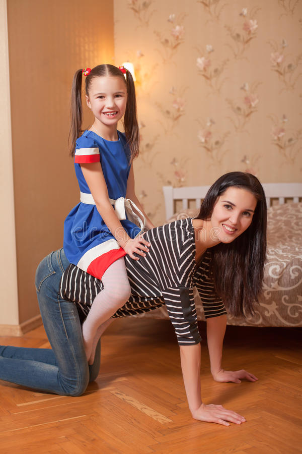 Συνεδρίαση μικρών κοριτσιών στην πλάτη της μητέρας της στοκ φωτογραφίες
