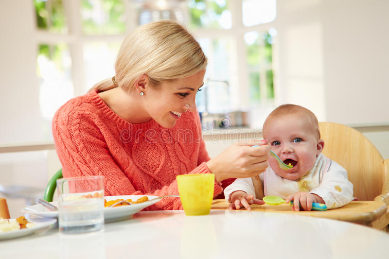 Συνεδρίαση μωρών σίτισης μητέρων στην υψηλή έδρα σε Mealtime στοκ εικόνες