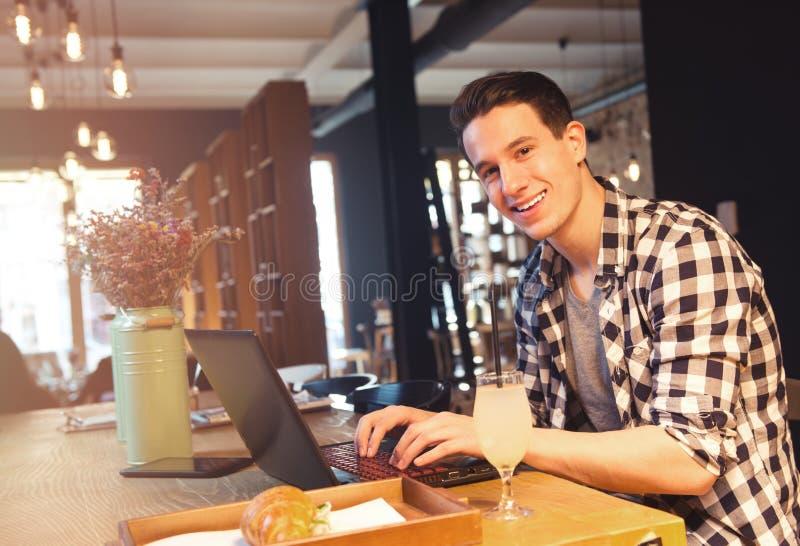 Συνεδρίαση νεαρών άνδρων σε έναν καφέ, που χρησιμοποιεί ένα lap-top στοκ φωτογραφία με δικαίωμα ελεύθερης χρήσης