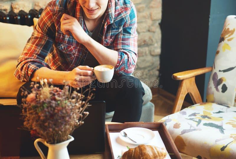 Συνεδρίαση νεαρών άνδρων σε έναν καφέ, που χρησιμοποιεί ένα lap-top στοκ εικόνες