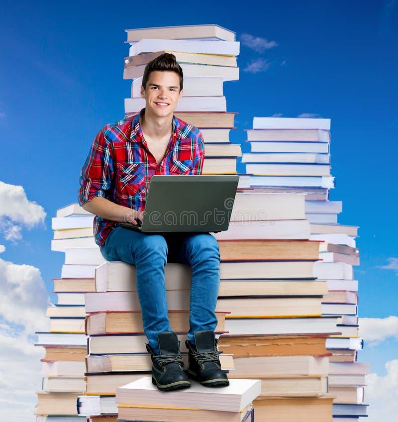 Συνεδρίαση νεαρών άνδρων σε έναν σωρό των βιβλίων με ένα lap-top στοκ εικόνα