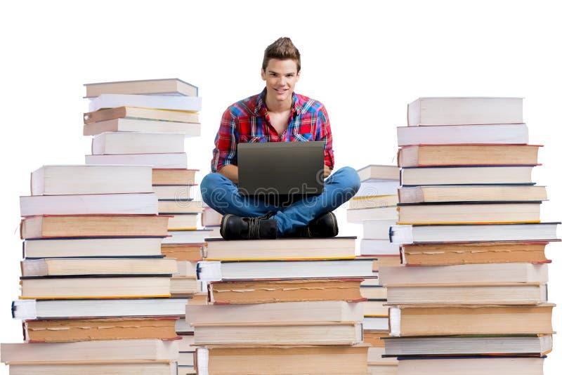 Συνεδρίαση νεαρών άνδρων σε έναν σωρό των βιβλίων με ένα lap-top στοκ φωτογραφίες με δικαίωμα ελεύθερης χρήσης