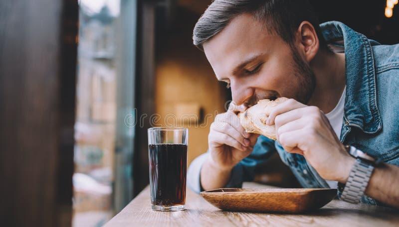 Συνεδρίαση νεαρών άνδρων σε ένα εστιατόριο και κατανάλωση ενός χάμπουργκερ στοκ φωτογραφίες