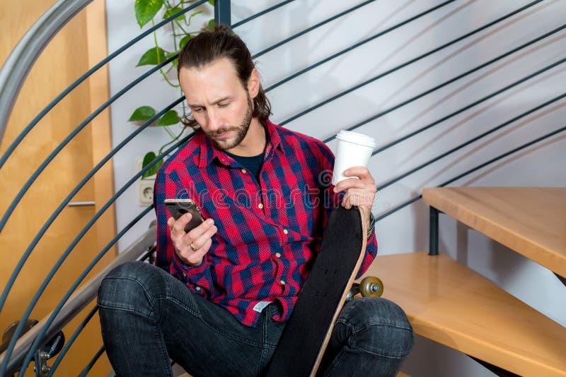 Συνεδρίαση νεαρών άνδρων στα σκαλοπάτια και χρησιμοποίηση του τηλεφώνου στοκ εικόνα