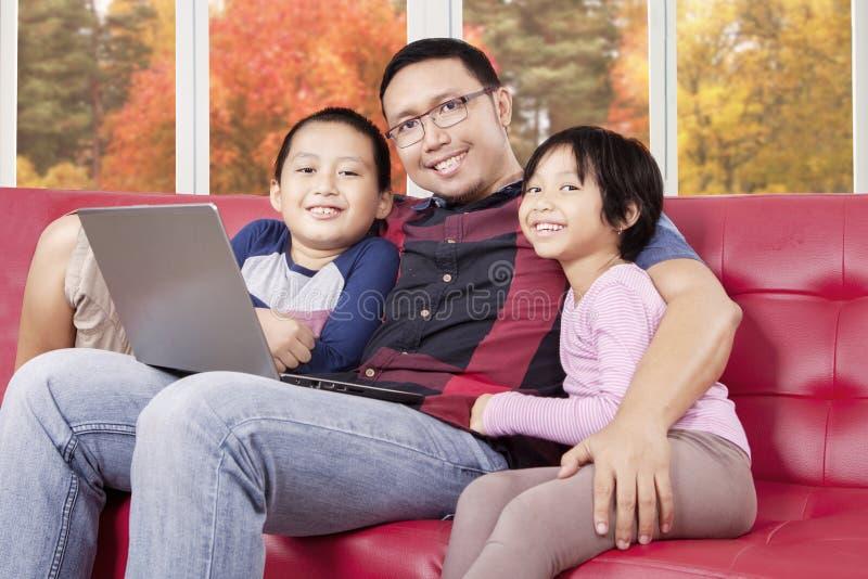 Συνεδρίαση νεαρών άνδρων στον καναπέ με τα παιδιά και το lap-top του στοκ φωτογραφία με δικαίωμα ελεύθερης χρήσης