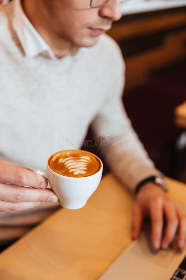 Συνεδρίαση νεαρών άνδρων στον καφέ κατανάλωσης καφέδων και χρησιμοποίηση του lap-top στοκ φωτογραφία με δικαίωμα ελεύθερης χρήσης