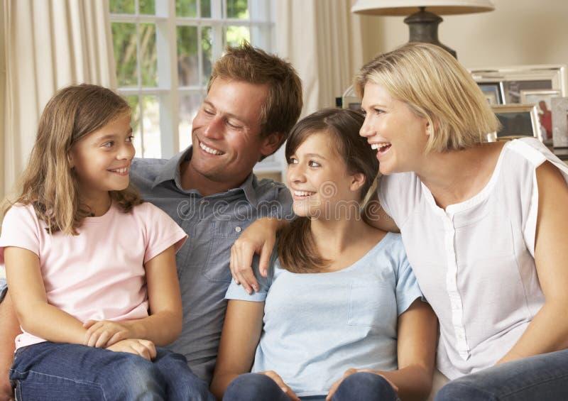 Συνεδρίαση οικογενειακής ομάδας στον καναπέ στο εσωτερικό στοκ φωτογραφία