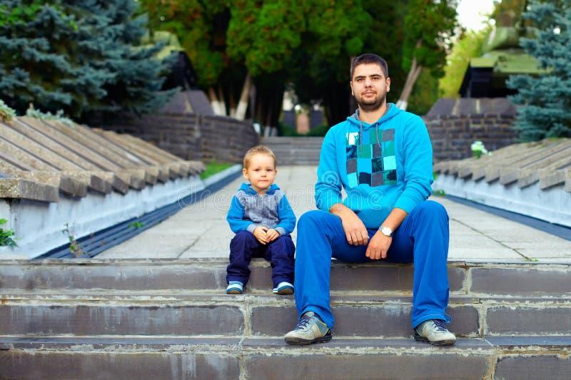 Συνεδρίαση πατέρων και γιων στα σκαλοπάτια στο πάρκο στοκ εικόνα