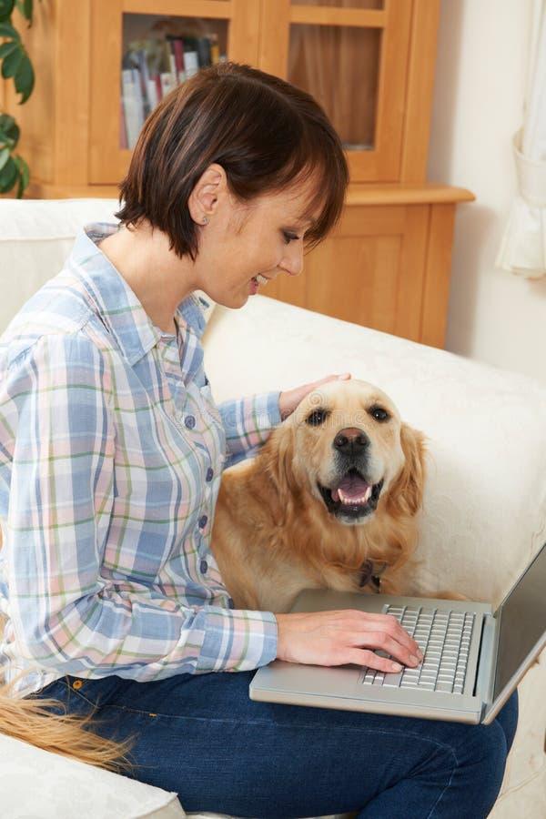 Συνεδρίαση σκυλιών δίπλα στον ιδιοκτήτη που χρησιμοποιεί το lap-top στοκ φωτογραφίες με δικαίωμα ελεύθερης χρήσης