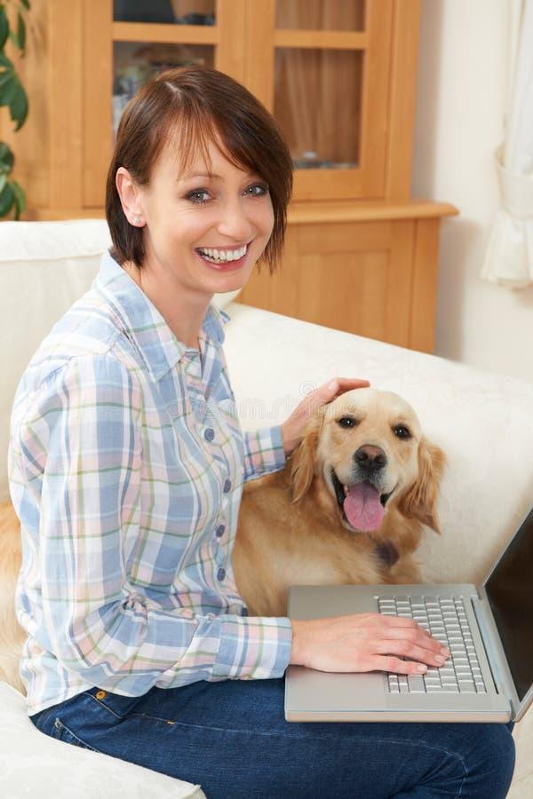 Συνεδρίαση σκυλιών δίπλα στο θηλυκό ιδιοκτήτη που χρησιμοποιεί το lap-top στοκ φωτογραφία