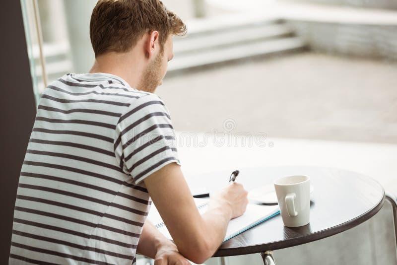 Συνεδρίαση σπουδαστών με ένα ζεστό ποτό και γράψιμο στο σημειωματάριο στοκ φωτογραφία