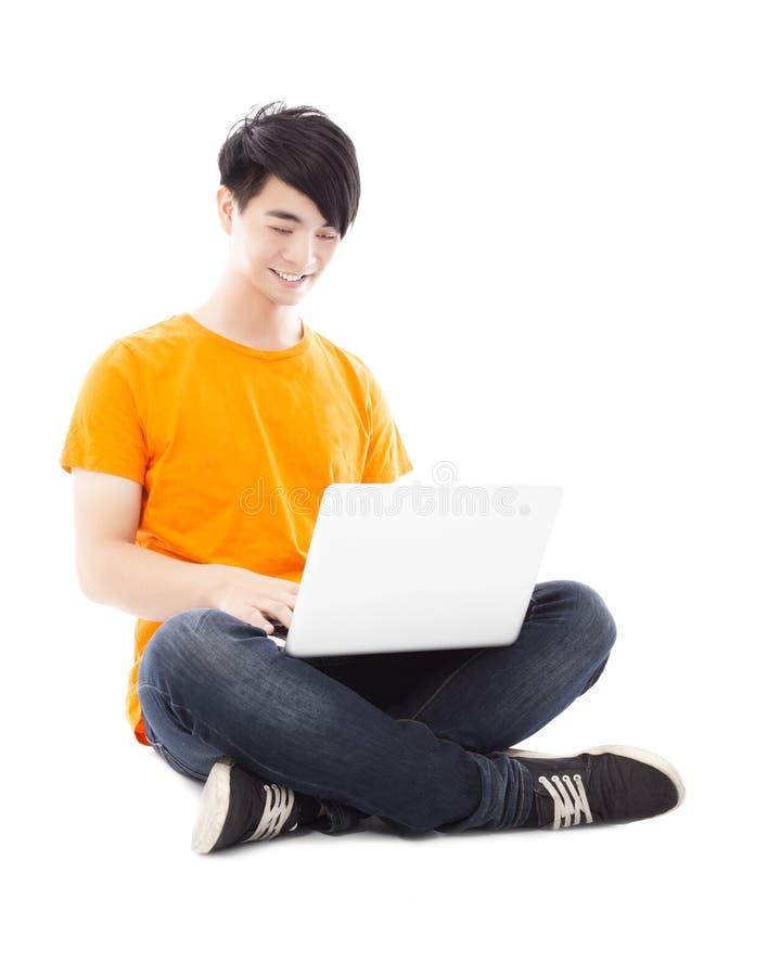 Συνεδρίαση σπουδαστών χαμόγελου νέα στο πάτωμα και χρησιμοποίηση του lap-top στοκ εικόνες