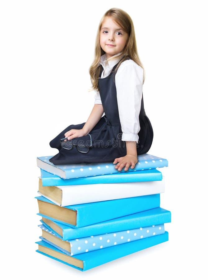 Συνεδρίαση σχολικών κοριτσιών παιδιών στο σωρό σωρών των βιβλίων που απομονώνεται στοκ εικόνα