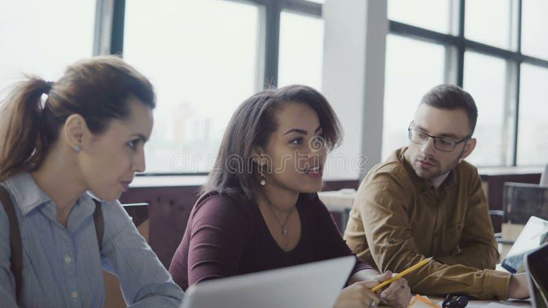 Συνεδρίαση των επιχειρησιακών ομάδων στο σύγχρονο γραφείο Δημιουργική νέα μικτή ομάδα ανθρώπων φυλών που συζητά τις νέες ιδέες με στοκ εικόνα