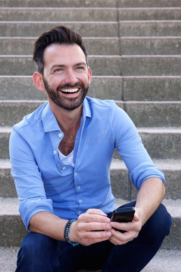 Συνεδρίαση τύπων χαμόγελου ώριμη υπαίθρια με το κινητό τηλέφωνο στοκ εικόνες