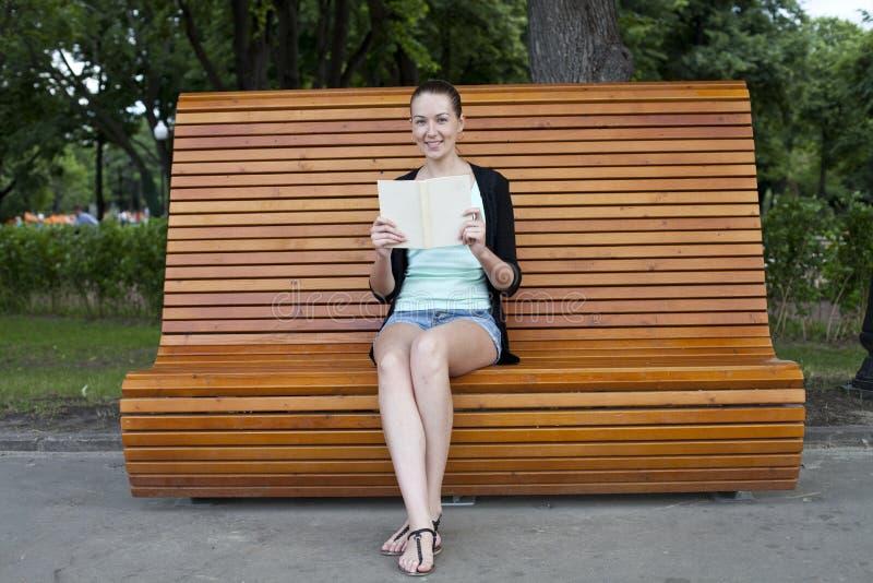 Συνεδρίαση Brunette σε έναν πάγκο σε ένα θερινό πάρκο στοκ εικόνες