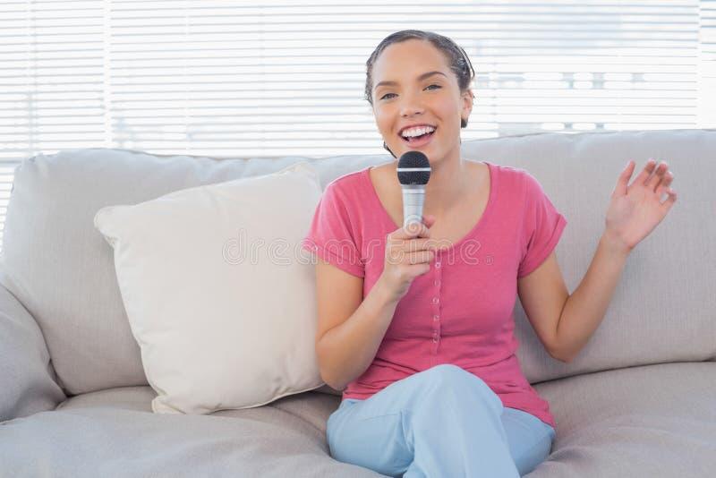 Συνεδρίαση Brunette στον καναπέ της που τραγουδά στο μικρόφωνο που εξετάζει τη κάμερα στοκ φωτογραφίες