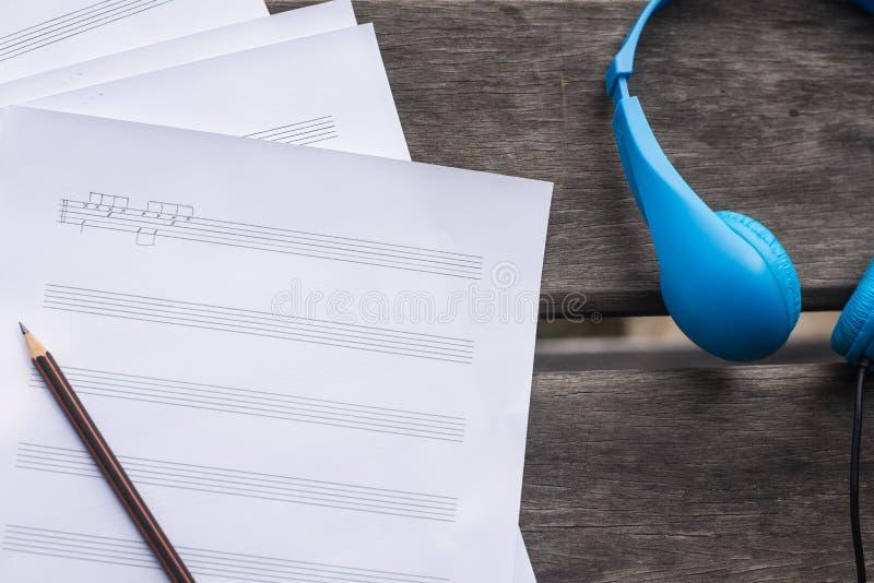 συνθέτοντας τη μουσική με το μπλε ακουστικό και στο ξύλινο γραφείο στοκ εικόνες