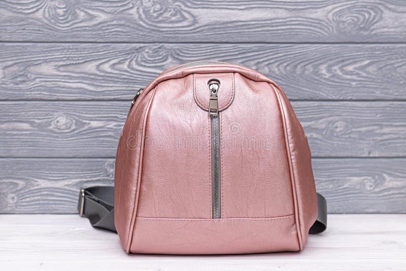 Συνθετικό δερμάτινο ροζ σακίδιο σε ξύλινο φόντο Οικολογική δερμάτινη τσάντα στοκ εικόνες με δικαίωμα ελεύθερης χρήσης