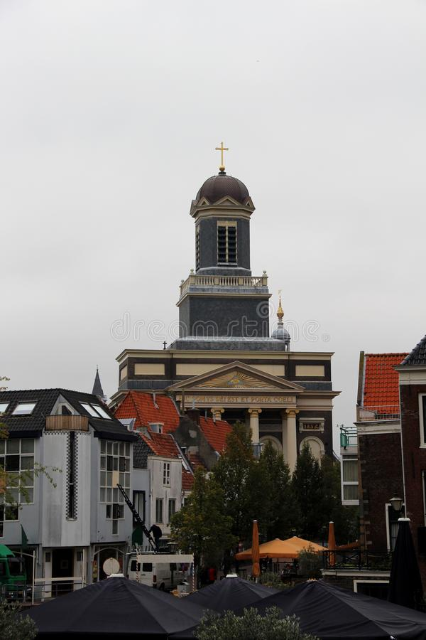 Συνολική άποψη σχετικά με μια ιστορική εκκλησία με το καμπαναριό που αυξάνεται στο νεφελώδη ουρανό στη νότια Ολλανδία Κάτω Χώρες  στοκ εικόνες