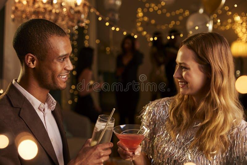 Συνομιλία ζεύγους δεδομένου ότι απολαμβάνουν το κόμμα κοκτέιλ από κοινού στοκ εικόνες