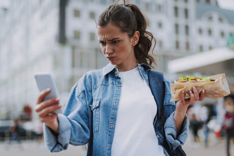 Συνοφρύωμ θηλυκό που κάνει το αστείο selfie με το χοτ-ντογκ στοκ φωτογραφία με δικαίωμα ελεύθερης χρήσης