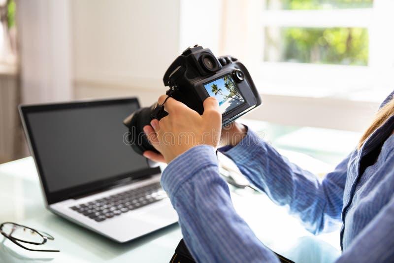 Συντάκτης που εξετάζει τη φωτογραφία στη κάμερα DSLR στοκ φωτογραφία