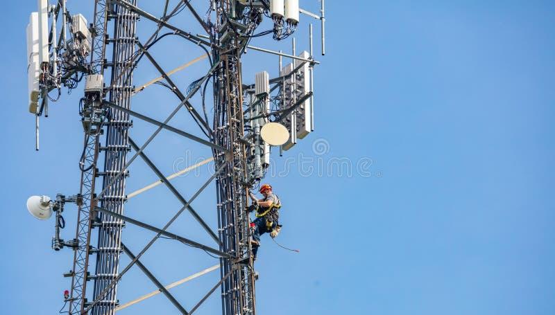 Συντήρηση επικοινωνίας Τεχνικός που αναρριχείται στον πύργο τηλεπικοινωνιών στο κλίμα μπλε ουρανού στοκ φωτογραφία