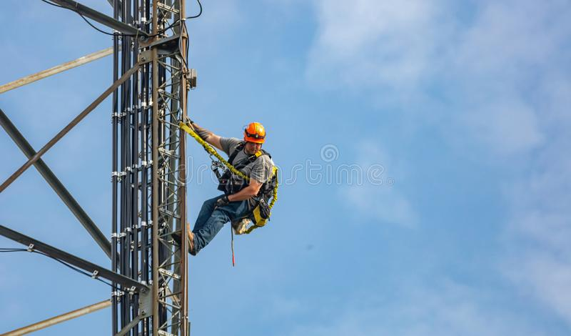 Συντήρηση επικοινωνίας Τεχνικός που αναρριχείται στον πύργο τηλεπικοινωνιών στο κλίμα μπλε ουρανού στοκ εικόνες