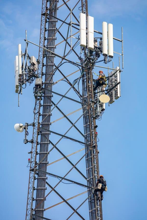 Συντήρηση επικοινωνίας Τεχνικός που αναρριχείται στον πύργο τηλεπικοινωνιών στο κλίμα μπλε ουρανού στοκ φωτογραφίες με δικαίωμα ελεύθερης χρήσης
