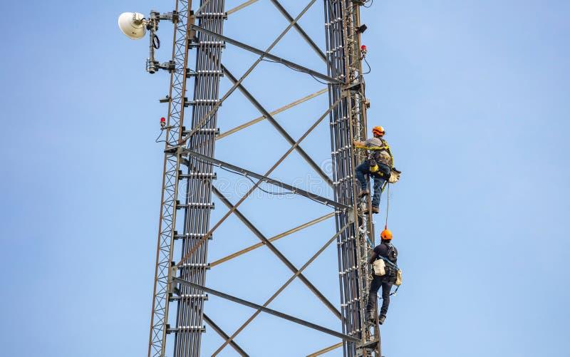 Συντήρηση τηλεπικοινωνιών Δύο άτομα επισκευής που αναρριχούνται στον πύργο στο κλίμα μπλε ουρανού στοκ εικόνα