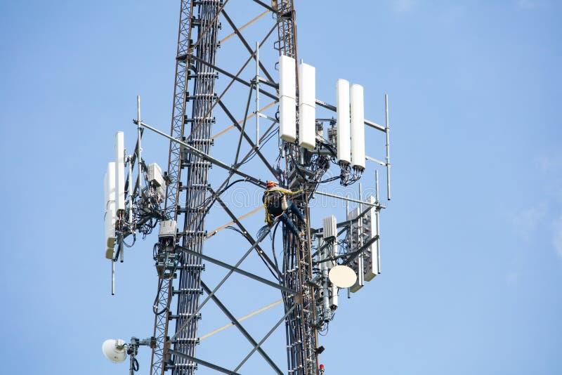 Συντήρηση τηλεπικοινωνιών Δύο άτομα επισκευής που αναρριχούνται στον πύργο στο κλίμα μπλε ουρανού στοκ εικόνες