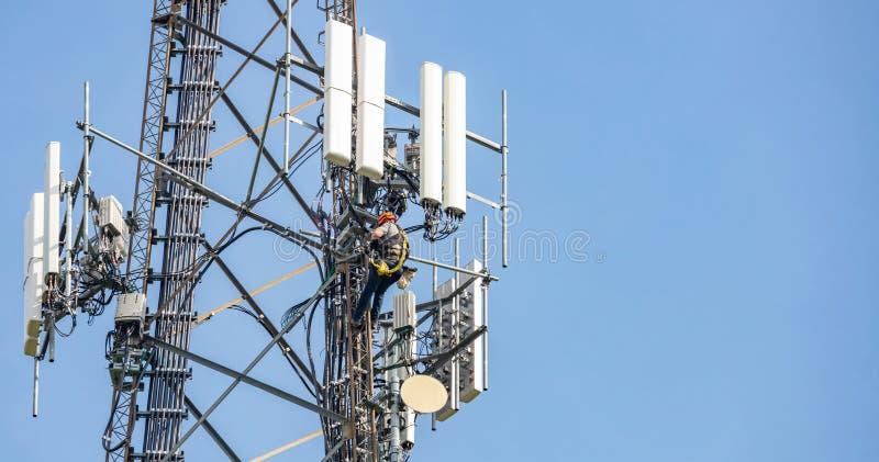 Συντήρηση τηλεπικοινωνιών Δύο άτομα επισκευής που αναρριχούνται στον πύργο στο κλίμα μπλε ουρανού στοκ φωτογραφία με δικαίωμα ελεύθερης χρήσης