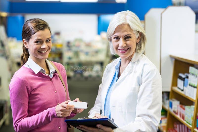 Συνταγές γραψίματος φαρμακοποιών για τον πελάτη στην περιοχή αποκομμάτων στο φαρμακείο στοκ εικόνες με δικαίωμα ελεύθερης χρήσης