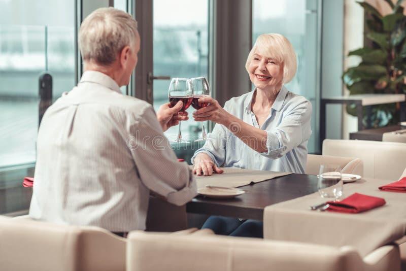 Συνταξιούχοι άνδρας και γυναίκα που πίνουν το κόκκινο κρασί από κοινού στοκ εικόνες