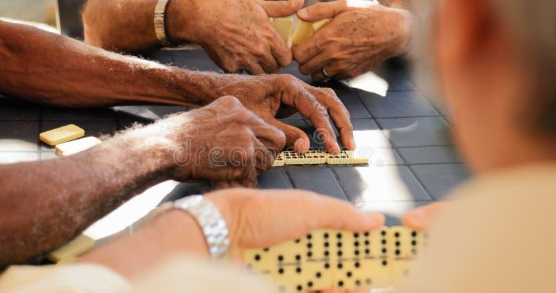 Συνταξιούχοι ηληκιωμένοι που παίζουν το παιχνίδι ντόμινο με τους φίλους στοκ εικόνες