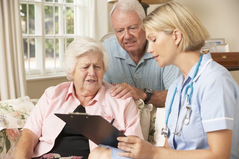 Συνταξιούχος ανώτερη γυναίκα που έχει τον έλεγχο υγείας με τη νοσοκόμα στο σπίτι στοκ φωτογραφίες