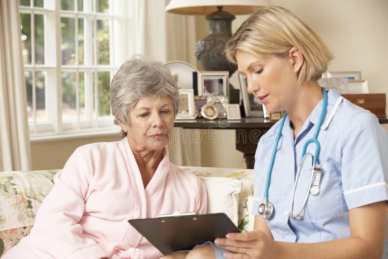 Συνταξιούχος ανώτερη γυναίκα που έχει τον έλεγχο υγείας με τη νοσοκόμα στο σπίτι στοκ εικόνες