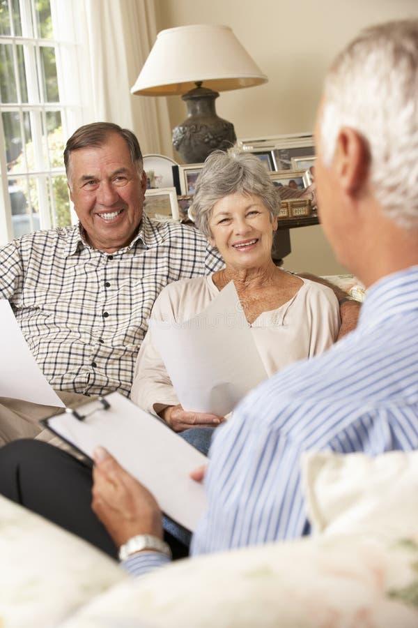 Συνταξιούχος ανώτερη συνεδρίαση ζεύγους στον καναπέ που μιλά στον οικονομικό σύμβουλο στοκ φωτογραφίες