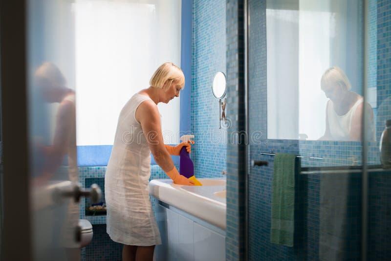 Συνταξιούχος γυναίκα που κάνει τις μικροδουλειές και που καθαρίζει το λουτρό στοκ εικόνα με δικαίωμα ελεύθερης χρήσης