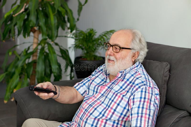 Συνταξιούχο άτομο με την άσπρη γενειάδα που προσέχει τη TV στοκ φωτογραφία με δικαίωμα ελεύθερης χρήσης